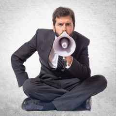 Businessman shouting by megaphone over white background