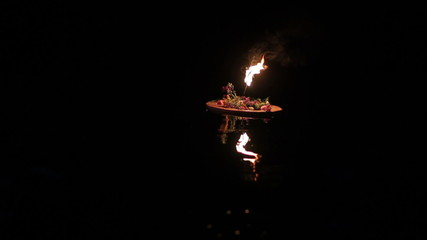 One wreath with torch floats down the river.