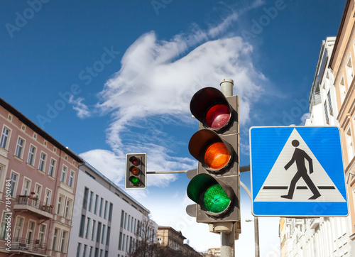 Traffic lights and pedestrian crossing sign in a city. - 78450784