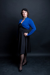 middle-aged woman wearing black dress and blue blouse stands