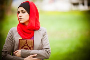 Muslim woman wearing hijab and holding a holy book Koran