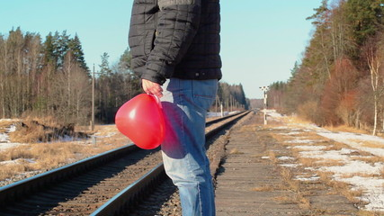 Man with red heart-shaped balloon near the railway