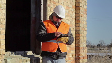 Construction employee with tablet PC near building
