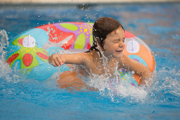 Girl (4-5) in swimming pool swimming in inflatable ring