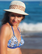 Happy smiling woman in hat on blue sea background