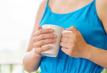 Young woman in blue dress enjoying a mug of beverage