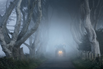 Ireland, Tractor on road at dusk