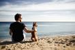 Caucasian man in sunglasses sitting in beach with friend's dog