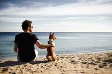 """Постер, картина, фотообои """"Caucasian man in sunglasses sitting in beach with friend's dog"""""""