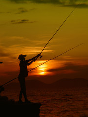Albania, Silhouette of boy fishing during sunset