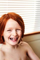 Portrait of smiling redhead boy (6-7)
