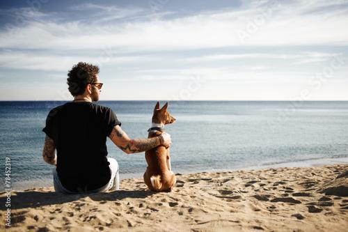 Leinwanddruck Bild Caucasian man in sunglasses sitting in beach with friend's dog