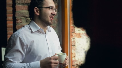 Businessman having a coffee break and relaxing at window.