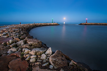 Italy, Lazio, Latina, Rio Martino, Scenic view of groyne in sea at sunrise