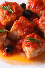 sea fish in tomato sauce with olives on a plate macro vertical