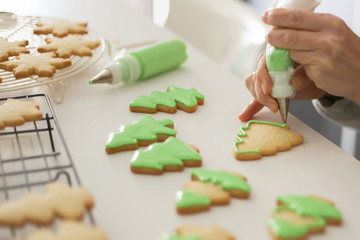 Woman painting cookies with green colored icing