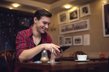 Young smiling attractive man uses his tablet in the lunchtime at