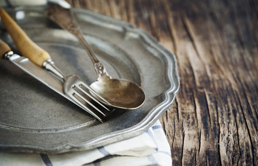 Close-up of vintage plate with fork, spoon and table knife