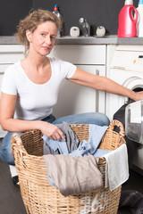 Frau lädt Wäsche in die Waschmaschine