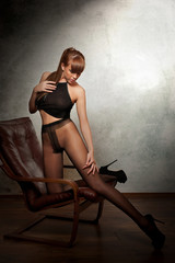 Attractive red hair model with black pantyhose sitting