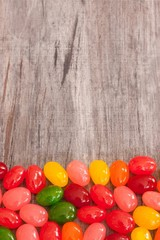 Easter jelly beans on wooden board with copy space