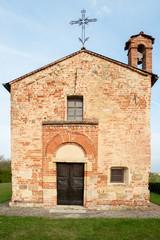 Small old romanic church, catholic religion, cross, grass