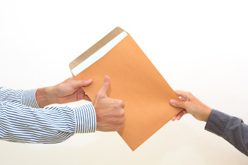 woman's hand passes envelope to male hand on white background
