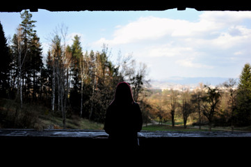 Silhouette of woman looking at view from abandoned ruin