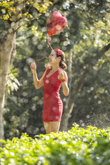 Woman with red heart shape balloon in a park
