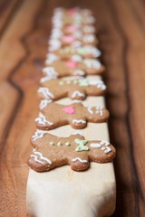 Gingerbread men in a row from the side on a wooden background