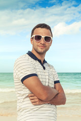 Caucasian man standing with sunglasses on sea coast