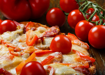 Delicious pizza with bacon, salami and cherry tomatoes