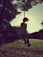 Girl swinging on rope swing, backlit image