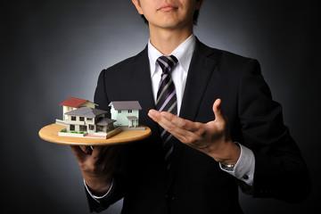 家の模型をたくさん紹介して住宅販売をしているスーツのビジネスマン