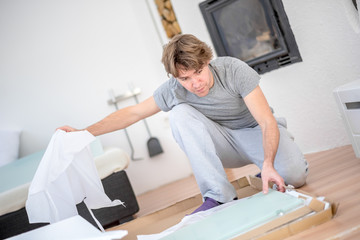 Man unpacking a package on the floor