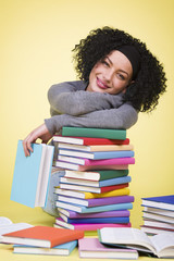 Joyous student girl reading surrounded by colorful books.