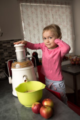Happy little girl making fresh apple juice