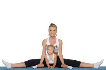 Mom and daughter do gymnastics on mat