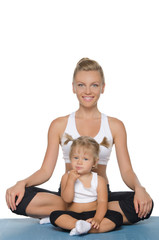 Mom and daughter doing yoga on mat