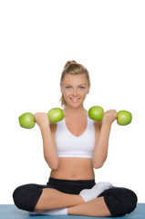 Young woman with dumbbells of green apples