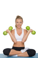Beautiful woman with dumbbells of green apples