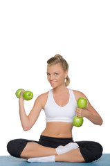 Happy woman with dumbbells of green apples