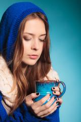 teen girl holding blue mug with hot drink