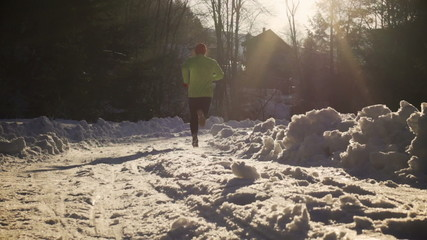 Man run at sunny day on snowy road, steady, slow motion 240fps
