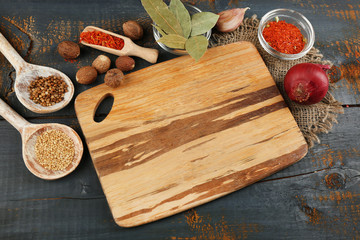 Different spices and herbs with cutting board