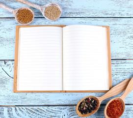 Przyprawa z przepisem książki na kolorowym tle drewnianego stołu