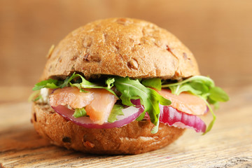 Sandwich with salmon on wooden background