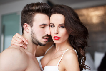 Sensual woman with red lips in hotel room with young lover