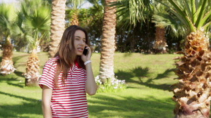 Beautiful young woman standing and talking on phone