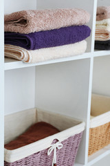 Colorful towels with wicker baskets on shelf of rack background